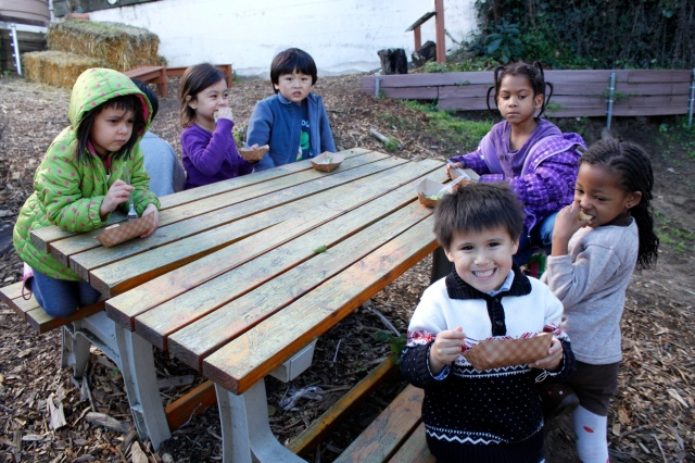 Kinders Having Salad by the Picnic Table